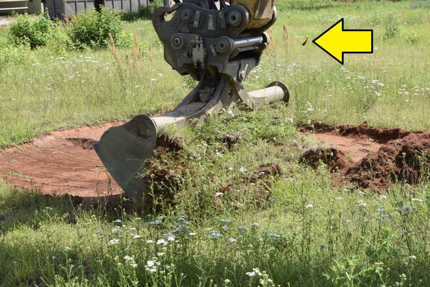 Die Anomalie wurde nach Oberflächen- bzw. Bohrlochdetektion gekennzeichnet (siehe Pfeil). Danach wird das Erdreich vorsichtig von einem unserer sprenggeschützten Bagger abgetragen.